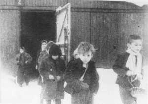 Soon after liberation, surviving children of the Auschwitz camp walk out of the children's barracks. Poland, after January 27, 1945. — United States Holocaust Memorial Museum