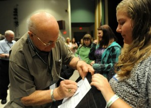 "Holocaust survivor Leslie Meisels, left, signs a program for Hudson Falls senior Taylor Bump during Wednesday's ""Remembering the Holocaust, Repairing the World"" event. Meisels, who currently lives in Toronto, stressed the importance of relaying his experience to young people ""so they remember and fight against discrimination, hatred and injustice."" Jason McKibben Glens Falls Post Star"
