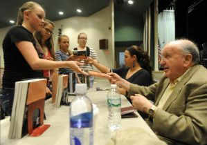 "Holocaust survivor Fred Spiegel sells and autographs copies of his book, ""Once the Acacias Bloomed,"" for students at Hudson Falls High School on Friday, May 24. Spiegel, who was liberated by U.S. troops as a young boy during World War II, spoke about his experiences and answered students' questions. (Jason McKibben -"