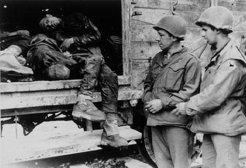 American soldiers view the bodies in one of the open railcars of the Dachau death train. USHMM