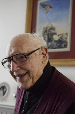 Ralph Leinoff, a Marine who fought at the Battle of Iwo Jima during World War II, stands in front of the drawing he modeled after Joseph Rosenthal's iconic photograph of five Marines and one Navy corpsman raising the American flag atop Mount Suribachi. (Portrait by Erica Miller, courtesy the Saratogian)